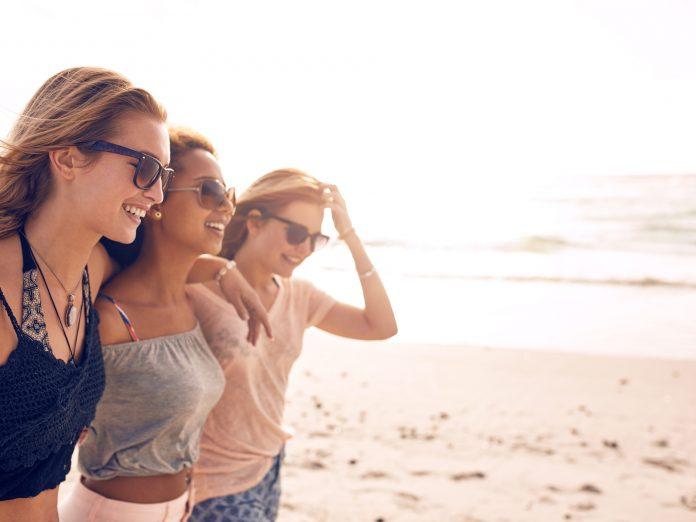 Happy young women walking on a beach