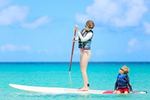 mother and son paddleboarding with life vests