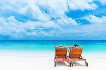 two beach chairs on beach overlooking ocean