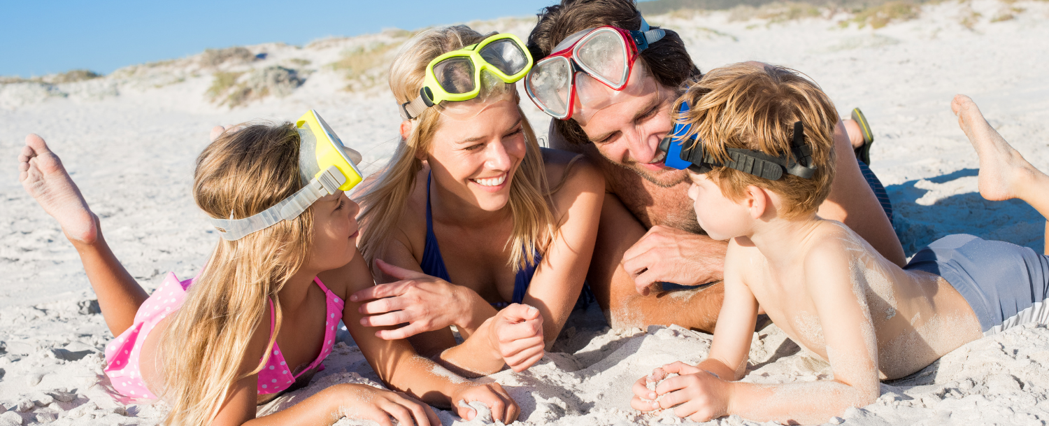 family laughing together in the sand while enjoying an Emerald Coast family vacation
