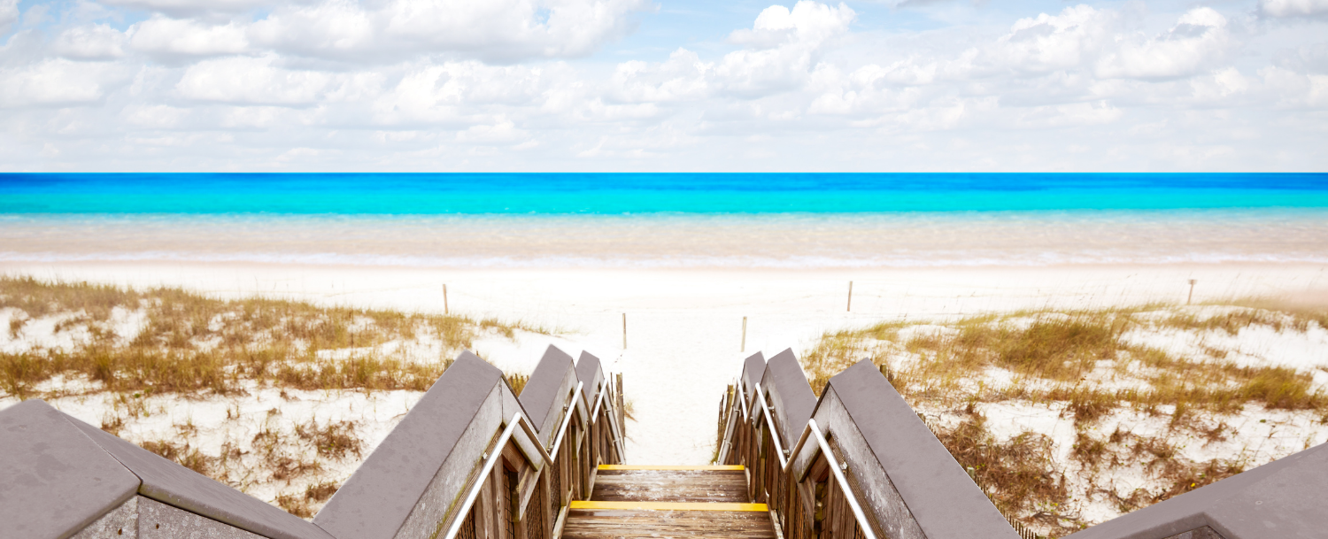 steps walking down to the beautiful Destin shoreline with white sand and blue water